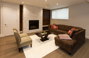 Newly renovated basement with ceiling lights and light brown wood floors and furniture and white stone fireplace and rug