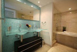 Picture of blue glass walls and sink bathroom. Tan marble shower, tub and flooring with backlighting on large mirron on the wall.