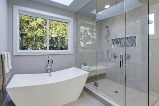 Picture of gray bathroom with white modern tub and large free staning shower enclosed in glass. large window across back of tub with white trim.