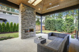 Image of a wood panel ceiling covered porch with a gray and white moder brick fireplace. Gray couch and matching coffee table. Concrete flooring ties the entire porch together.