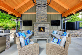 Picture of a back porch with a cedar wood ceiling. Gray floor to ceiling stone firepace and outdoor kitchen. Two couches and two chairs of natural fibers facing each other.