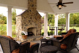Picture of a outdoor living room under a covered porch with a tan stone fireplace. Dark brown furniture and ceiling fan.