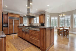 Oak kitchen with wood floors and modern appliances in a room with many windows