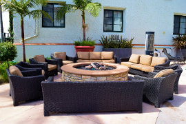 Photo of a patio with dark brown furniture facing a large stone round fire pit. Surrounded by palm trees and greenery.