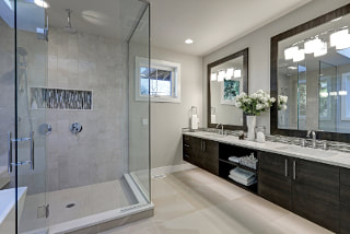 Picture of country french bath with large gray tile standup shower. Flat dark wood cabinets and mirror trim that sit over light counters and sinks. Light gray floor tiles with recessed lighting.