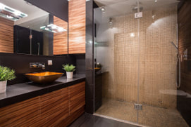 Picture of a modern washroom with black counters and grained wood cabinets. Large tan tile standup shower with rain shower head.