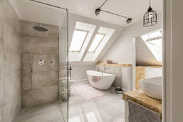 Gray and white bathroom picture with modern tub and stand up shower. Gray marble flooring with rustic black iron lighting. Two large roof angled skylights brighten the room.
