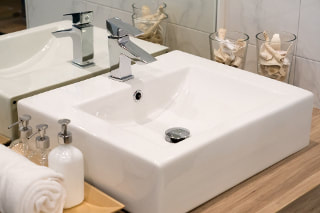 White ceramic square modern sink sitting on a wood counter with stainless steel faucets.