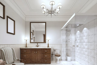 Photo of traditional bathroom with white tile shower and walls. Dark wood trimmed mirror, picture frames and cabinests. White waynes coating around walls and traditional ceiling lights and shaded lamps on counters next to sink.